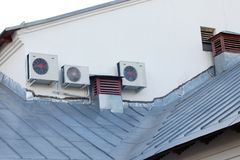 Air conditioning system and old ventilation pipes  on house roof stock image