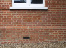 Brick wall of house with part of window showing and air brick - ideal background stock photo