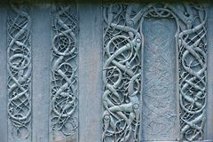 External wooden wall carved decoration of the medieval Urnes Stave church with viking motifs covered with tar in Ornes, Norway. Royalty Free Stock Images