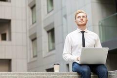 Externalización de trabajo y el preguntarse del hombre de negocios adulto joven Fotos de archivo