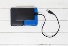 Externe Festplatten USBs auf hölzernem Hintergrund Lizenzfreie Stockbilder