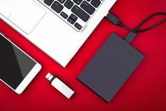 Externes Festplattenlaufwerk schloss an den Laptop-, USB-Blitz-Antrieb und Smartphone auf einem roten Hintergrund an Stockbild