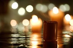 Extinct candle with reflection. Against defocused candlelight background Royalty Free Stock Photo