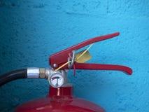 Extincteur de couleur rouge sur un fond bleu dans des lieux industriels image libre de droits