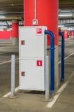 Extincteur et tuyau d'incendie dans le parking de mail Photographie stock