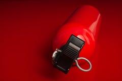 Extincteur se trouvant sur une surface rouge Photographie stock libre de droits