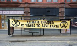 Extinction Rebellion Climate Change Warning In Manchester. Sign warning of climate change put up over a bus stop during the  Extinction Rebellion Party event in royalty free stock images