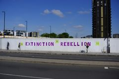 Extinction Rebellion name and logo spray painted onto hoarding of construction site stock image
