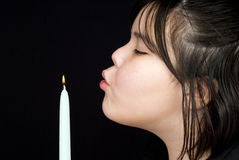 Extinguish. Closeup of a young girl blowing out a candle's flame, shot against a dark background Royalty Free Stock Image
