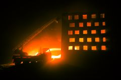 Extinguish the fire of a private house at night. Toy fire truck with long ladder and burning building at night. Fire alarm concept. Selective focus royalty free stock photo