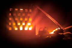 Extinguish the fire of a private house at night. Toy fire truck with long ladder and burning building at night. Fire alarm concept. Selective focus royalty free stock image