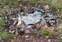Extinguished campfire close-up. Extinguished fireplace with ash and remains of wood lined with stones on the ground in a circle royalty free stock photos