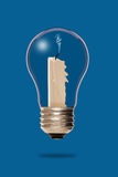 Extinguished candle inside a light bulb Royalty Free Stock Photography