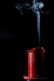 Extinguished candle of red color Royalty Free Stock Images
