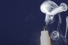 Extinguished candle with smoke on blue background stock photography