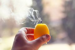 Extinguished candle in a hand on blurred nature background. Extinguished candle with smoke in a hand on blurred nature background stock photos