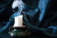 Extinguished Candle With Smoke. One extinguished candle with smoke on nice fabric background stock image