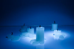 Extinguished candles in blue. On the reflective surface royalty free stock images