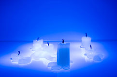 Extinguished candles in blue. On the reflective surface stock image
