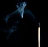 Extinguished the match with smoke. On black background stock image