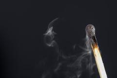 Extinguished match with smoke on dark background Stock Image