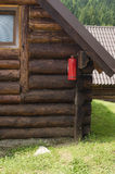 Extinguisher in the corner. Fire extinguisher in the corner of a wooden house royalty free stock images