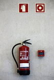 Extinguisher on the wall. View of a red bottle extinguisher on the wall along with sinaletics Stock Photography