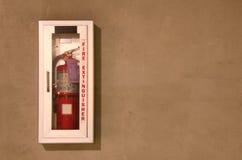 Extintor en un caso de cristal montado en la pared Imagen de archivo