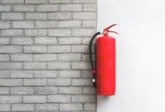 Extintor no fundo branco da parede de tijolo imagem de stock
