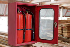 Extintores na pilha obscura de madeira no armazém Foto de Stock
