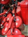 Extintores rojos Muchos extintores rojos en la tierra Di?xido de la espuma, de carbono, polvo y agua fotos de archivo