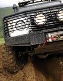 Extrémité conduisant le véhicule tous terrains sur la route de montagne de saleté Images stock