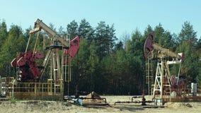 Extração do petróleo por Pumpjacks em um poço de petróleo em Rússia video estoque