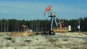 Extração do petróleo por Pumpjacks em um poço de petróleo em Rússia filme