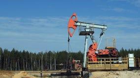 Extração do petróleo por Pumpjacks em um poço de petróleo em Rússia, movimento lento filme