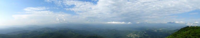Extra bred panorama av berg under April med snöig kullar, blå himmel med moln arkivbilder