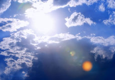 Extra-Bright Sun and Cloudscape. With vibrant color and intentional lens flare for dramatic effect - can be used for environmental, solar energy and/or Royalty Free Stock Photo