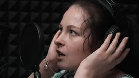 Extra close up view of young girl singing song. Close up of attractive woman in headphones. Close up of beautiful girl with blue e stock video footage