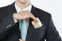 Extra earnings. Frontal chest view of a young man in a dark suit on the front pocket holding a 50-euro note Stock Image
