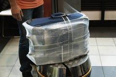 Extra emballage av bagage på flygplatsen för turen, arbetaren slår in resväskan med en genomskinlig film arkivbild