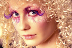 Extra long lashes. Girl like a doll with curly blond hair and extravagant make-up with extra long lashes Royalty Free Stock Photos