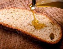 Extra maagdelijke olijfolie die op brood wordt gemotregend royalty-vrije stock afbeeldingen