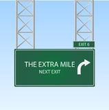 The Extra Mile. Image of a highway sign with an exit to The Extra Mile against a blue sky background royalty free illustration