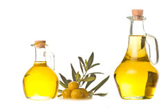 Extra olive oil two bottles isolated. Extra olive oil two bottles and olives with leaves isolated on a white background Stock Photo