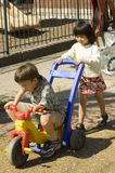 Extra Power. A young girl pushes an older boy on a tricycle Royalty Free Stock Image