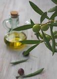 Extra-reine Olivenölflasche und grüne olivas Lizenzfreie Stockfotos
