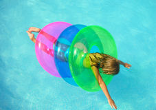 Extra safe swimmer. A young girl floating in three floats in a swimming pool Stock Image
