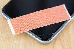 Extra strong fabric plaster on broken smart phone with cracked s. Creen, on wooden background, soft focus royalty free stock photo