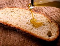 Extra virgin olive oil being drizzled onto bread Royalty Free Stock Images