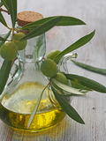 Extra-virgin olive oil bottle and green olivas Stock Photos